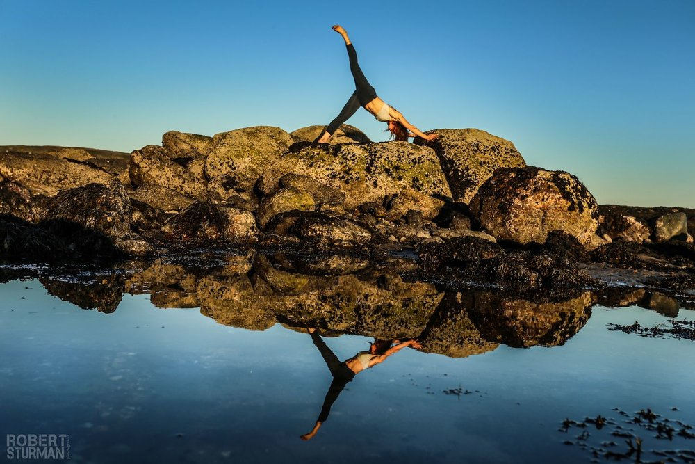Robert Sturman photograph of a yoga pose on rocks above the water