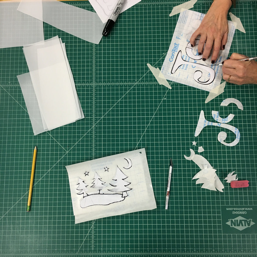 Cutting contact paper to use as a stencil.