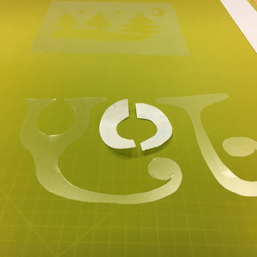 Applying contact paper to a screen as a stencil.