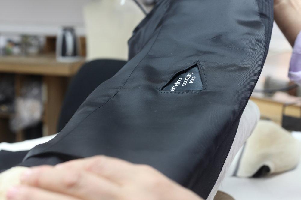 La réalisation de la boutonnière, notamment la boutonnière milanaise,représente un travail de 2h ainsi que 180 points de fil de soie.Broderie de la mouche: environ 80 points de fil de soie viennent finir et consolider la fente arrière d'une veste.Pose de bouton: choisis dès le départ, la Maison propose une impressionnante collection de boutons: nacre, or, onyx noir, lapis-lazuli, etc. -