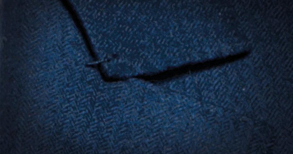 Détail unique du tailleur, la Travetta est une petite bride cousue main venant renforcer l'angle entre le col et le revers. -