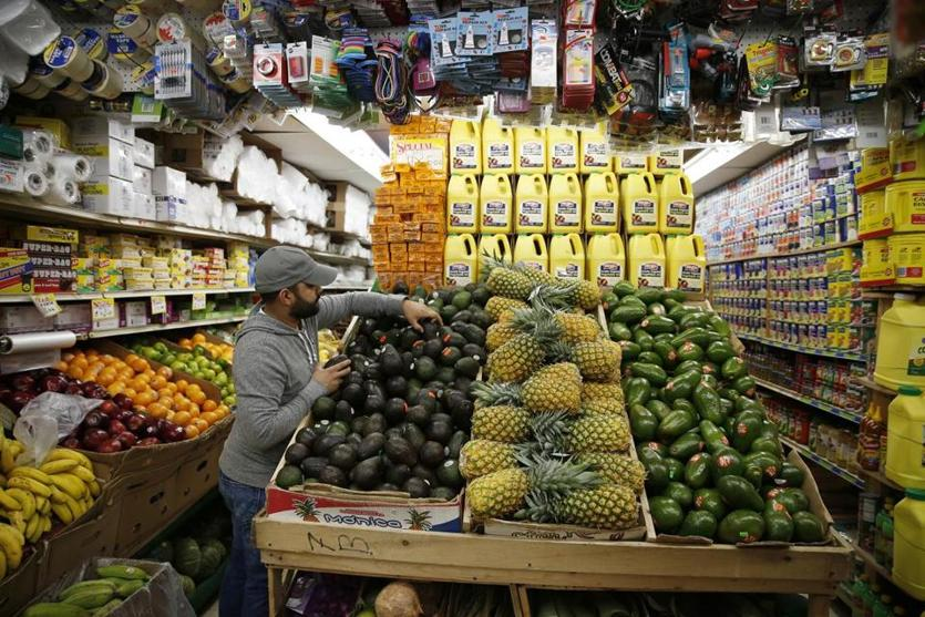 A customer reaches for avocados inside Mello's Supermarket in Lawrence