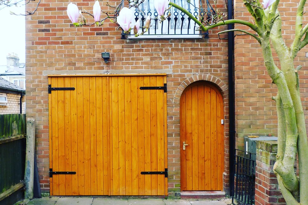 Stained pine garage doors for a home in Cambridgeshire.