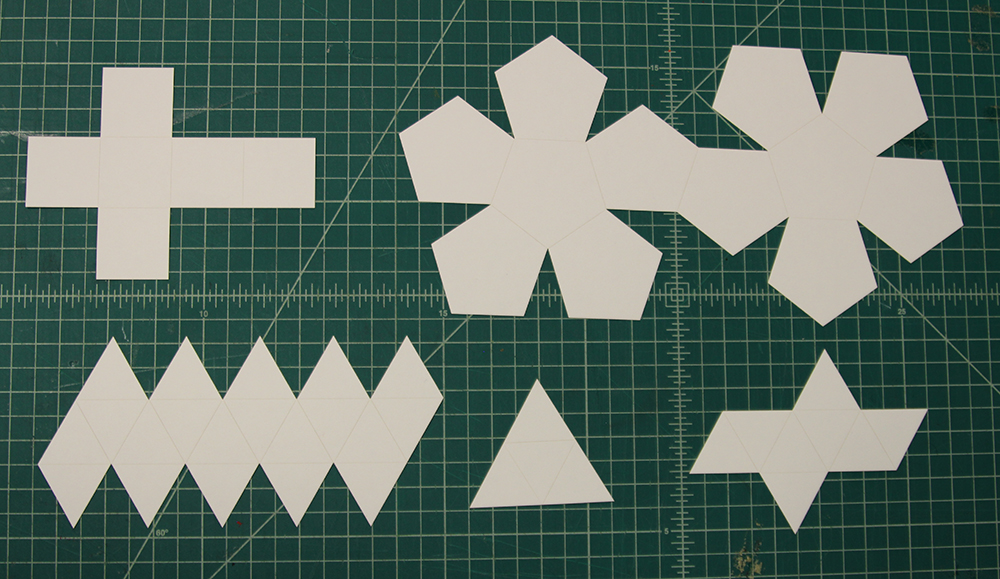 Laser cut platonic solids with scored grooves for easy folding, laid flat.