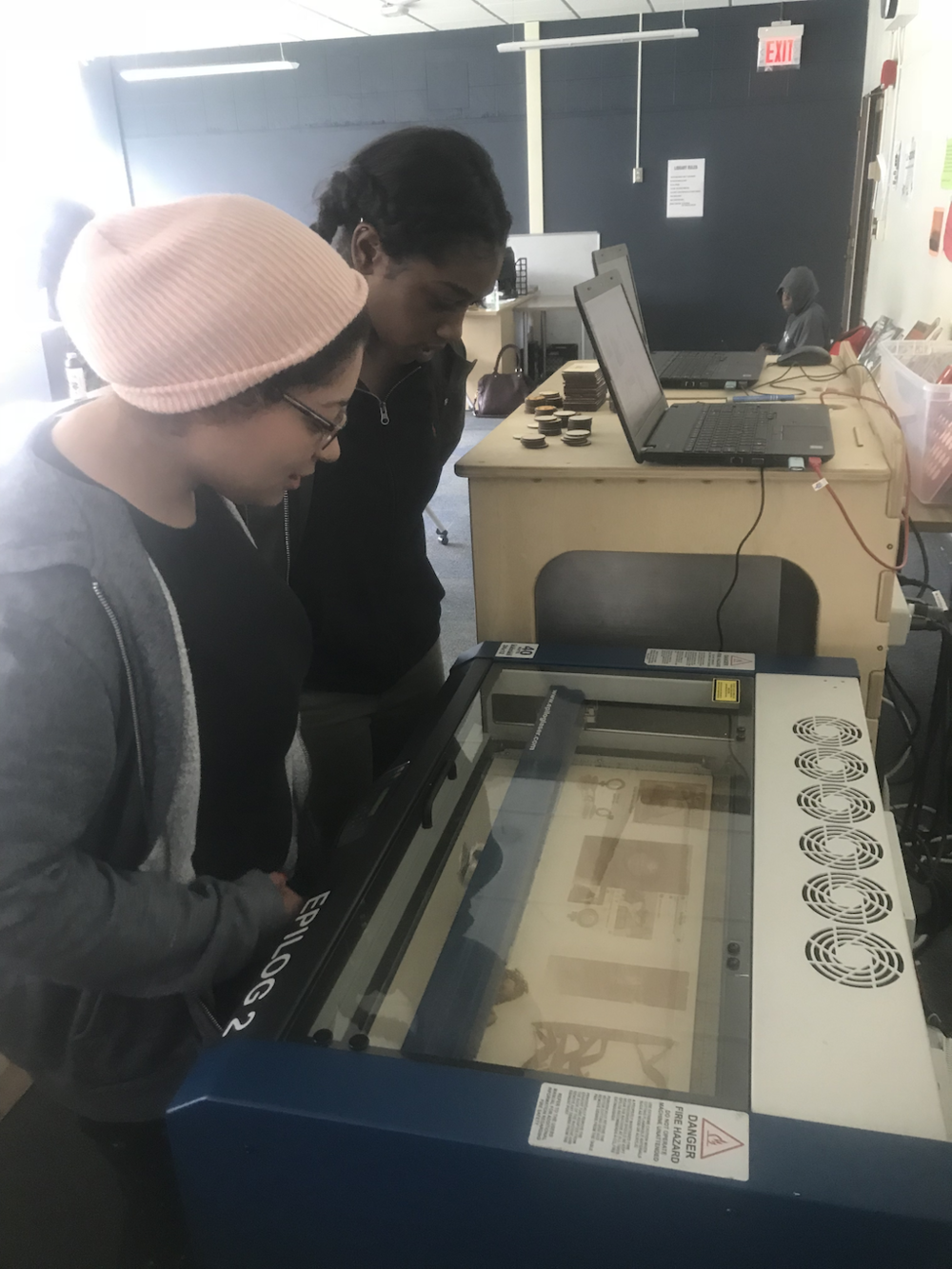 Students watching laser cutter burn their project pic. Courtesy of the author.