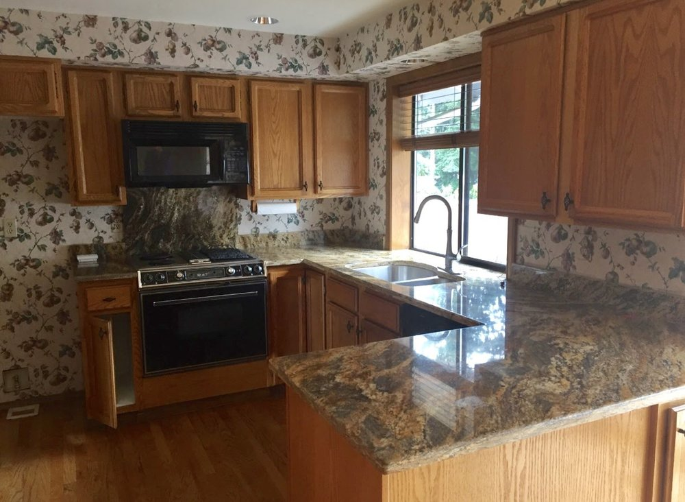 """The only """"update"""" the previous owner did before us, was changing the countertops. I don't know why in the world someone would pick that granite with the wallpaper."""