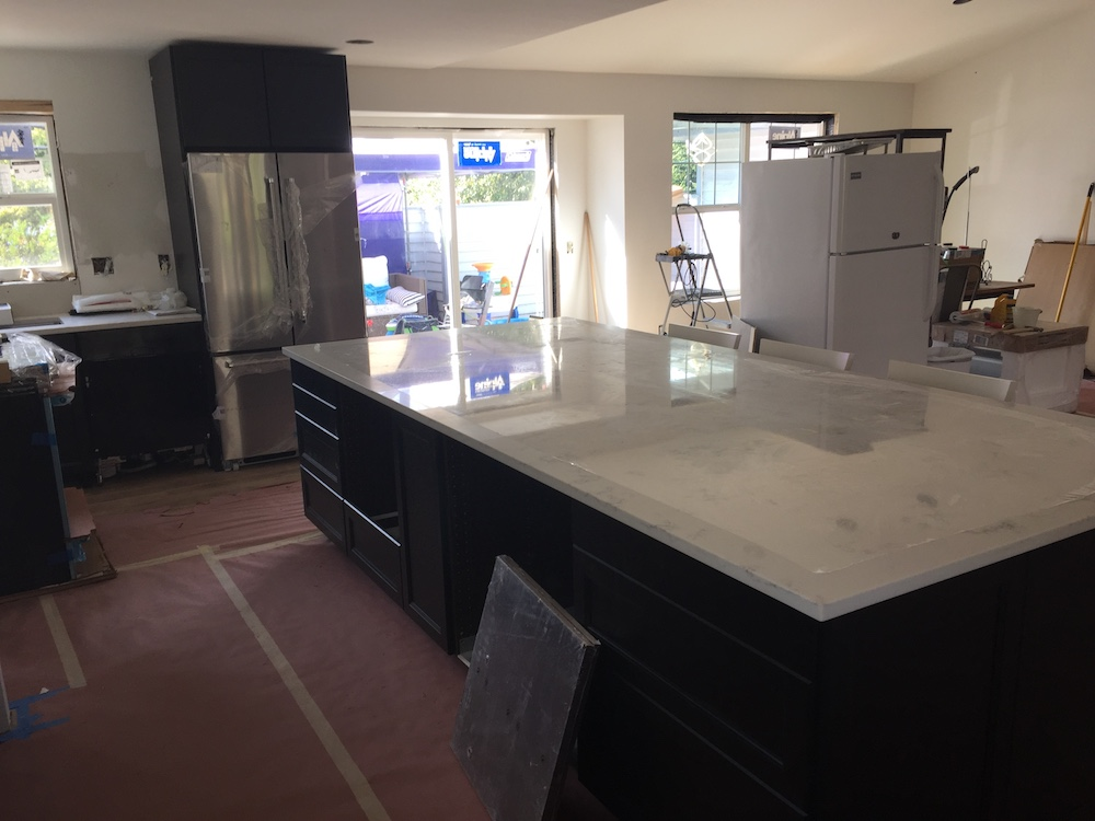 "Our Island is 2"" short on length and width from a whole slab. I wanted to center the island between the original kitchen and dining room to incorporate the ""buffet area"" where the previous dining room was."