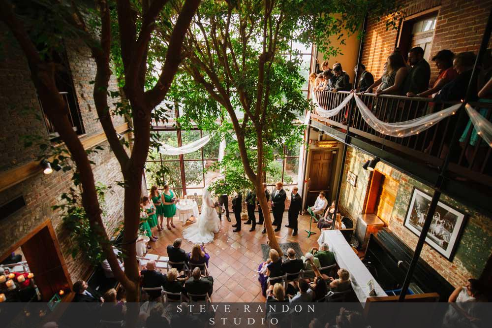 An indoor French Quarter style balcony overlooks our two-story atrium, where beautiful ceremonies are held under the canopy of two ficus trees. -