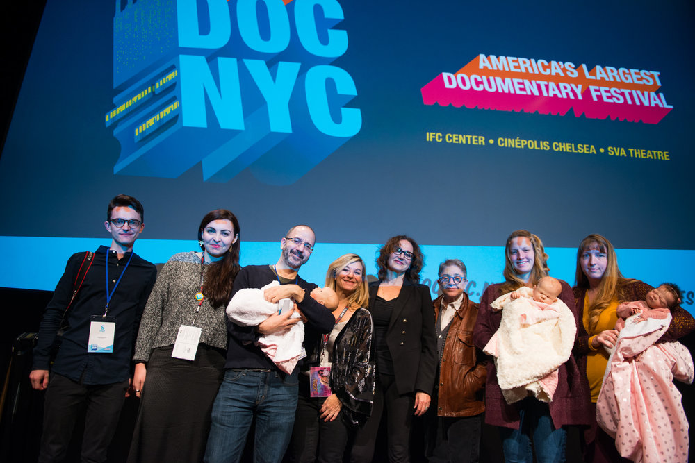 From left to right: Igor Myakotin (cinematographer), Dumitrita Pacicovschi (producer), Basil Tsiokos (DOC NYC Director of Programming, Melody Gilbert (director), Danielle Knafo (consulting producer), Joy Tomchin (producer), the artist who makes reborn dolls with her daughter and three reborn babies. Photo by Allison Stock - DOC NYC