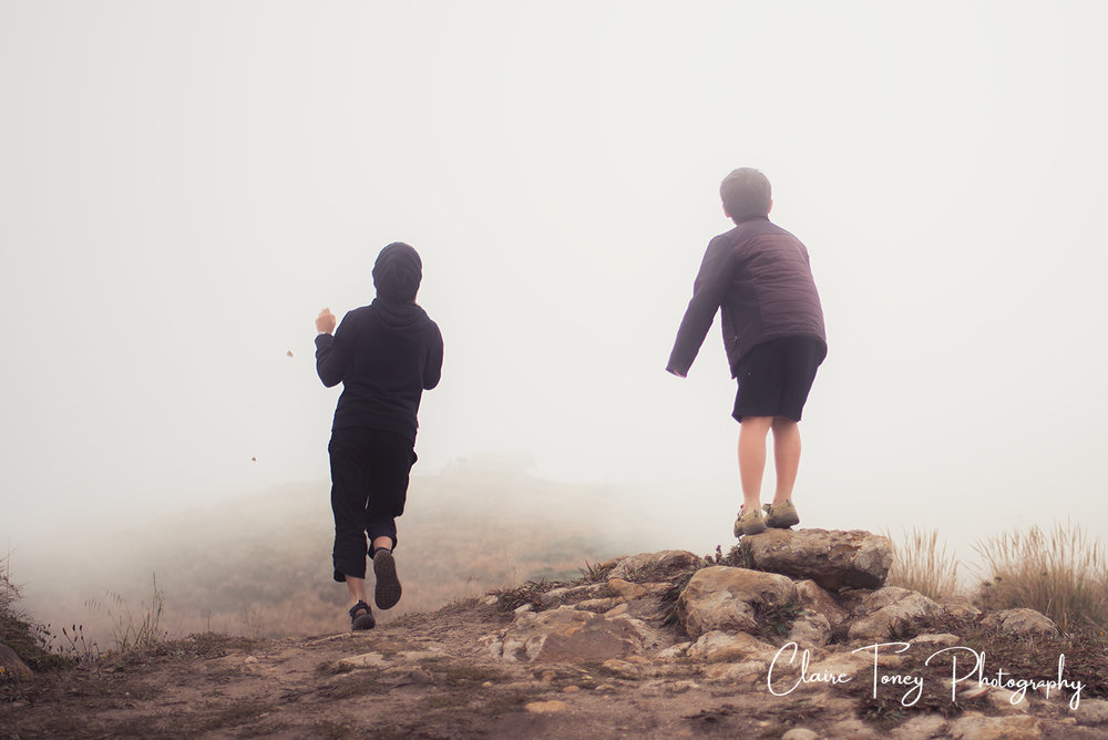 A girl chasing a butterfly in the fog. Her brother is balancing on a rock behind her.