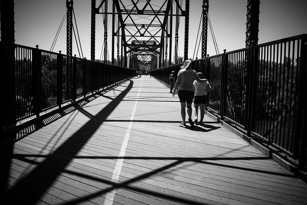 Black and white photo of a mom and her two kids walking on a bridge.