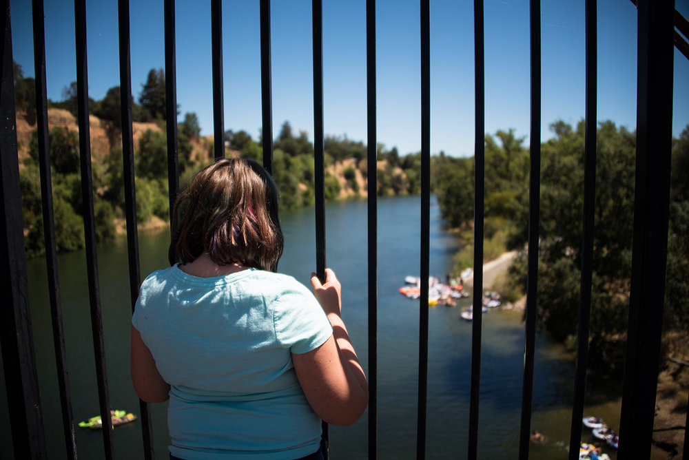 Young girl looking at the American River from the Red Bridge.