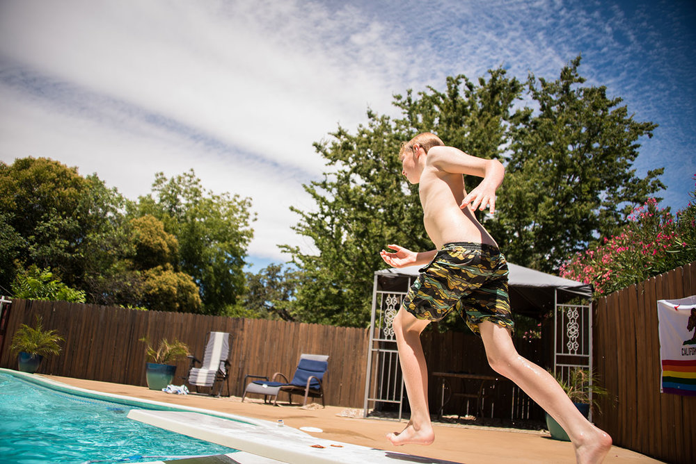 Boy running onto a diving board and into the pool.