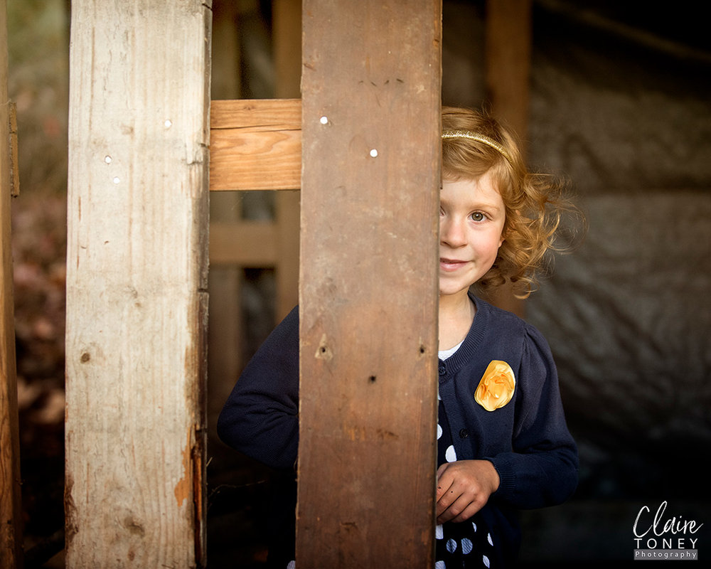 Girl half hidden behind a wooden post, looking at the photographer