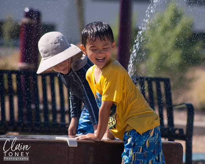 Young boy playing at a water table, laughing next to a boy wearing a hat.