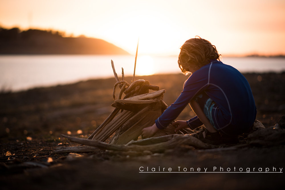 Little boy creating a driftwood teepee on the beach during golden hour at Folsom Lake