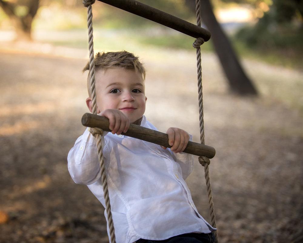 A little boy hanging onto a ladder swing.