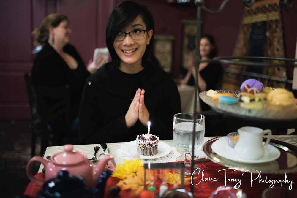 Smiling girl with a cupcake and birthday candle at Dash of Panache Teahouse Roseville CA Documentary Photography Claire Toney