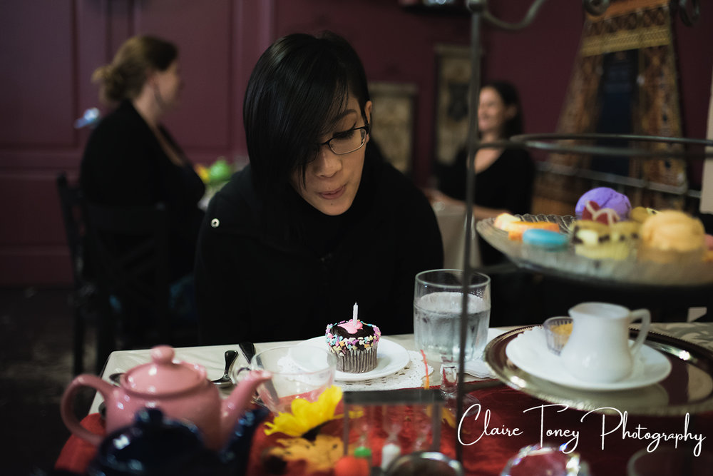 Blowing out a candle on a cupcake at Dash of Panache Teahouse Roseville CA Documentary Photography Claire Toney