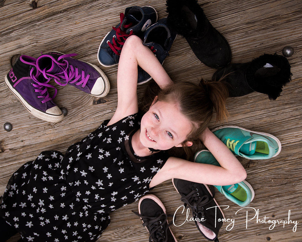 tween girl laying on wooden floor with her shoes surrounding her