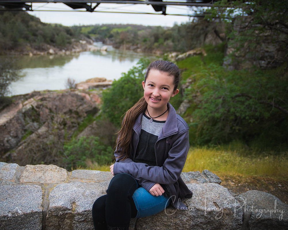 Tween girl sitting in lookout area with view of Folsom Rainbow Bridge behind her