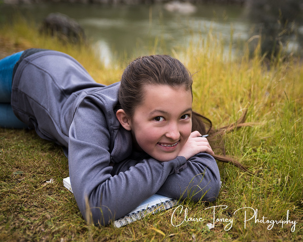Tween girl laying on grass on top of a sketch book