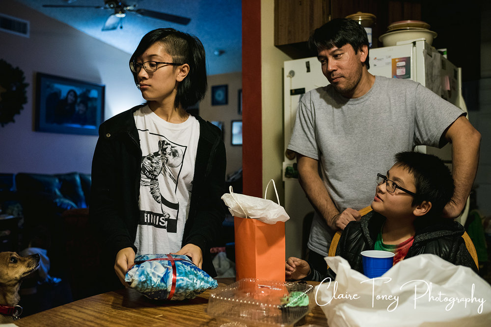 Family looking at dog at the dining room table with girl opening gifts