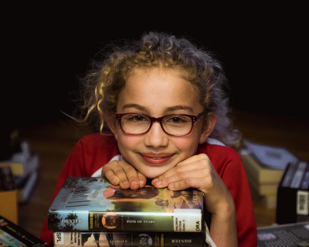 Tween girl resting on books