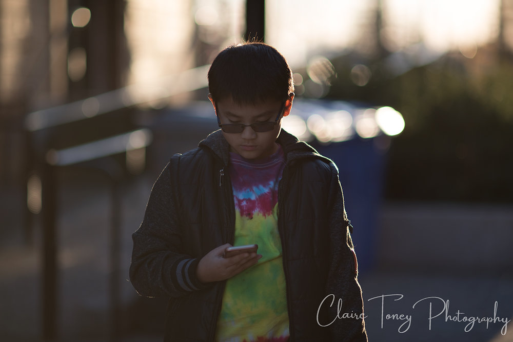 boy standing holding a phone