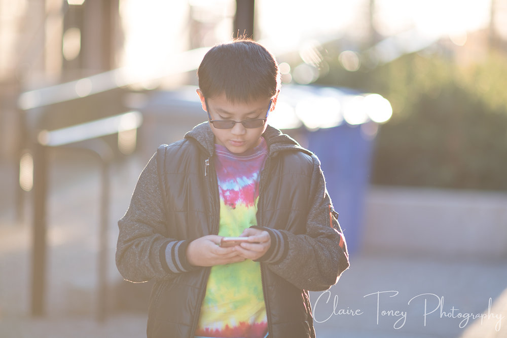 hazy photo of boy holding a phone