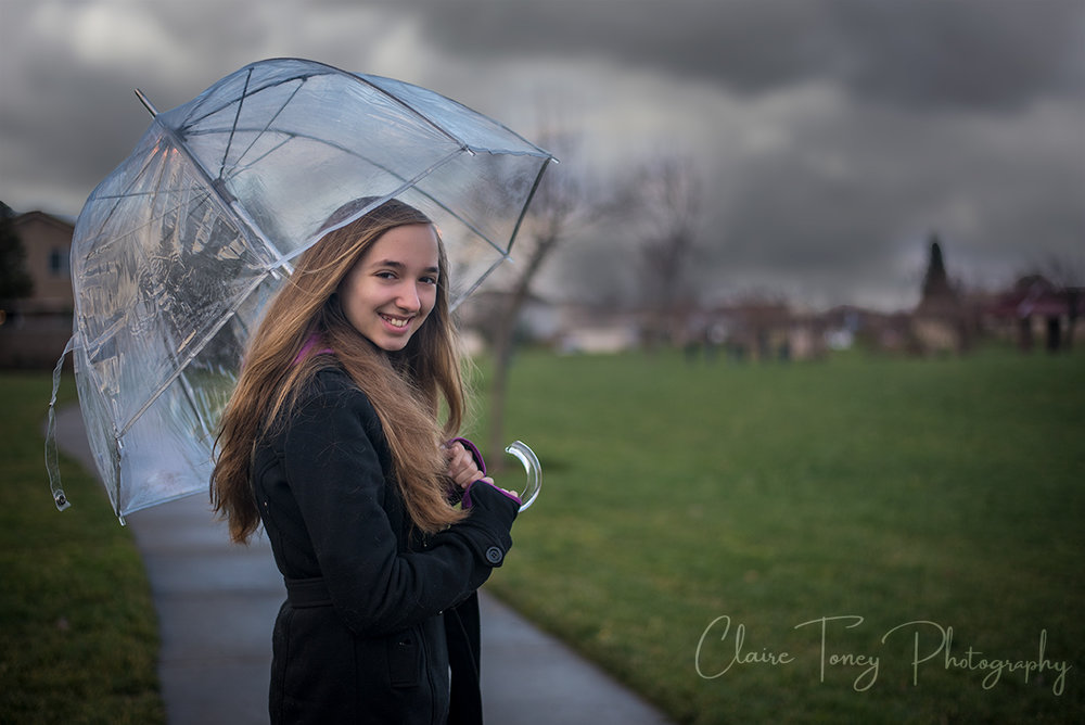 Tween girl holding an umbrella and there are dark forbidding clouds in the sky behind her