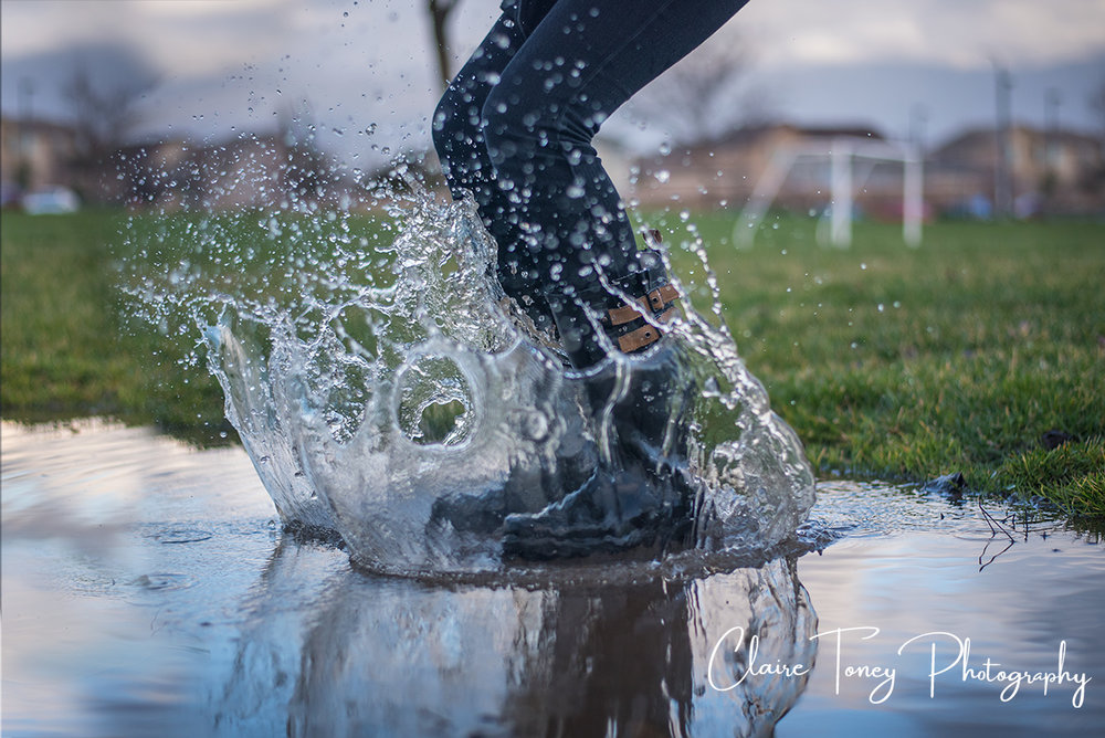 boots splashing water in a puddle