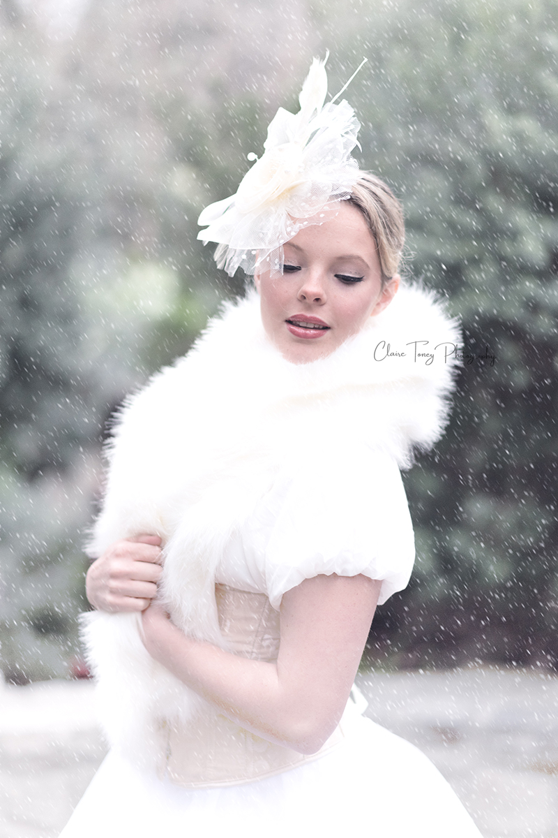 Teen girl wearing a white fascinator and dressed in a winter wrap during a styled winter photo shoot
