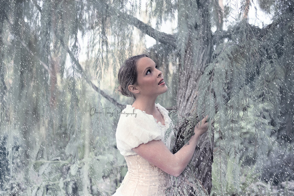 Teen girl wearing a light colored corset and peasant top next to a tree looking up during a snowfall