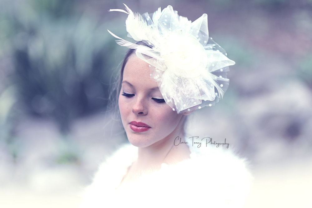 Girl wearing a white fascinator looking down