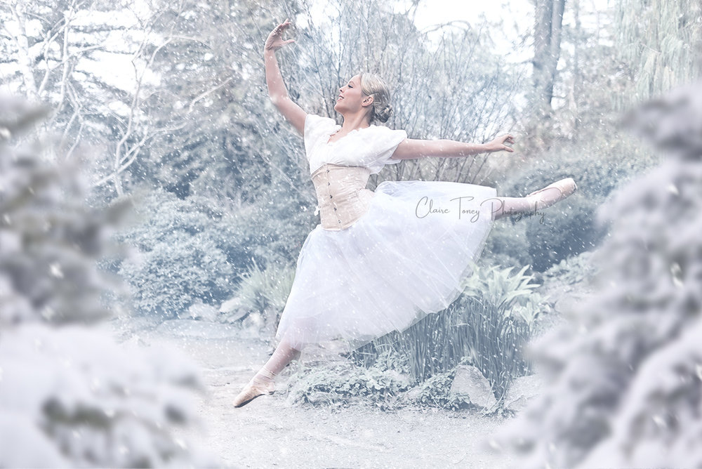 Teen ballerina wearing a white tutu, light colored corset, and peasant top performing a ballet jump in the snow