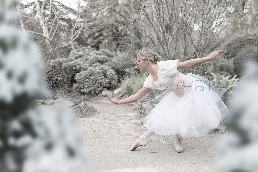 teen ballerina posing during a snow fall. she is wearing a white tutu, peasant top, and light colored corset