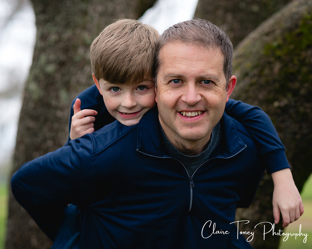 Son piggybacking on dad in front of a tree