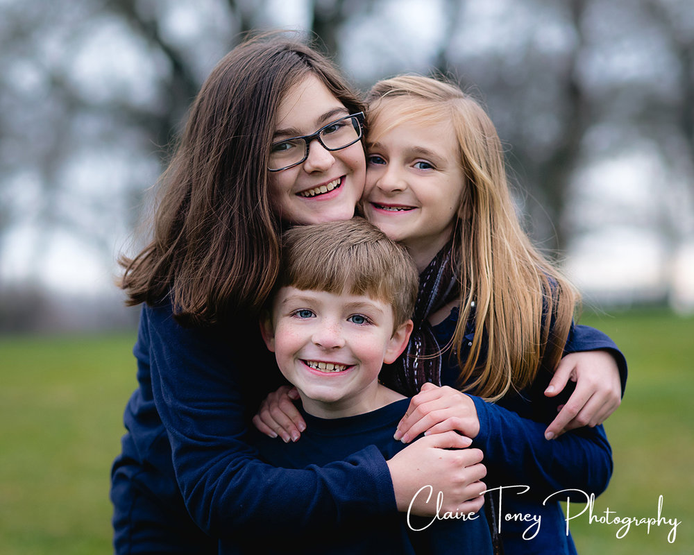 Two sisters and their brother smiling at the camera