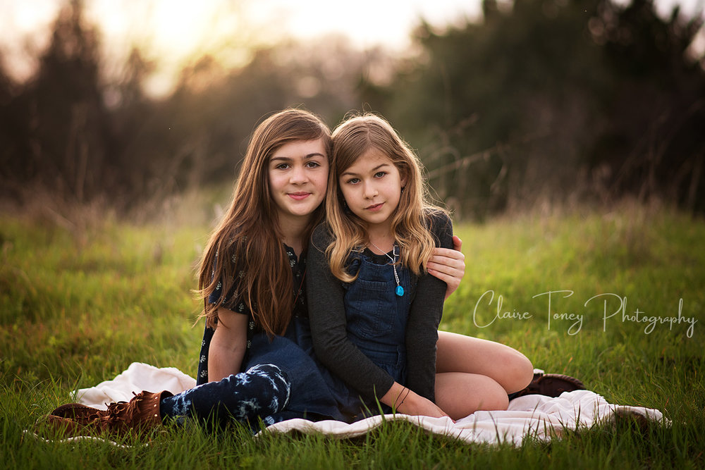Two sisters child portrait at a park, taken during sunset.