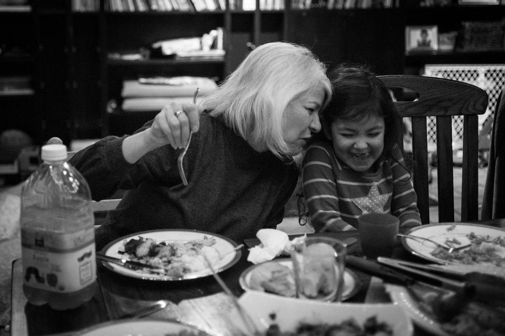 Grandmother making granddaughter giggle at dinner table