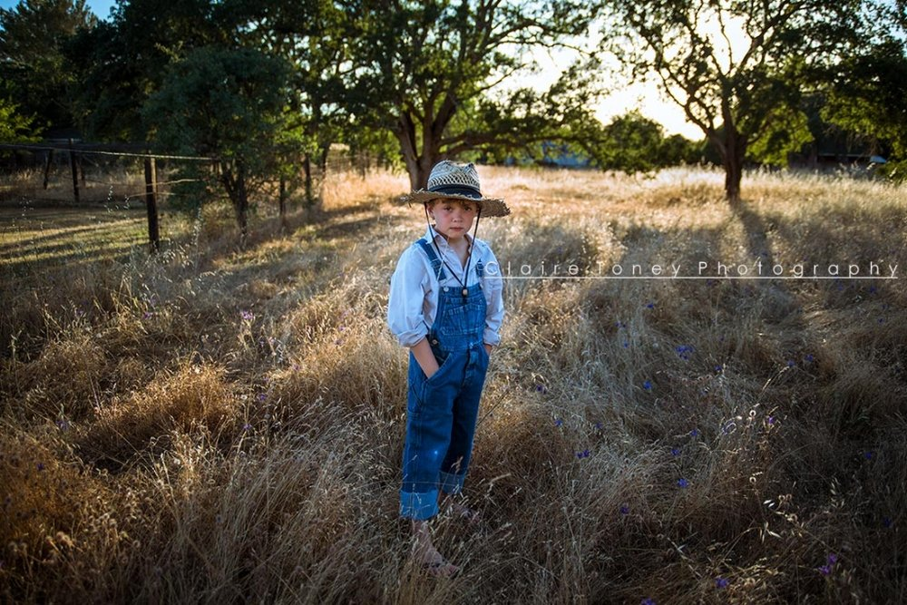 Boy wearing overalls and a straw hat for a Huckleberry Finn styled child portrait session. Claire Toney Photography, Sacramento Photographer