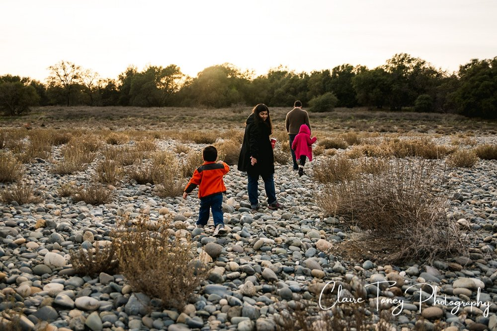 Family walking across a river of rocks with a mother holding out her hand to her young son