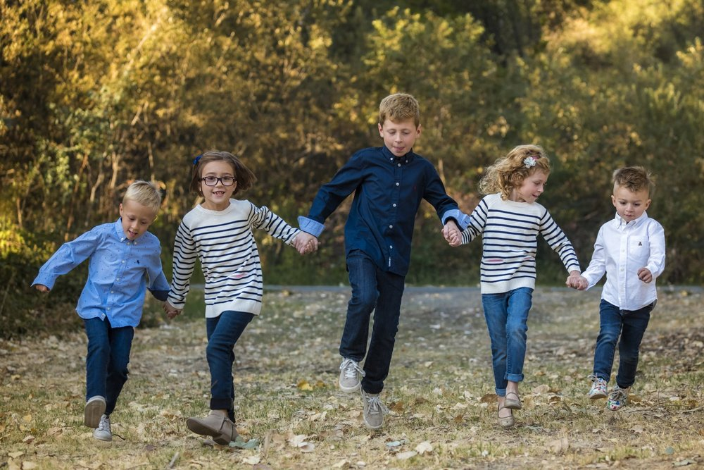 five children holding hands and skipping on grass