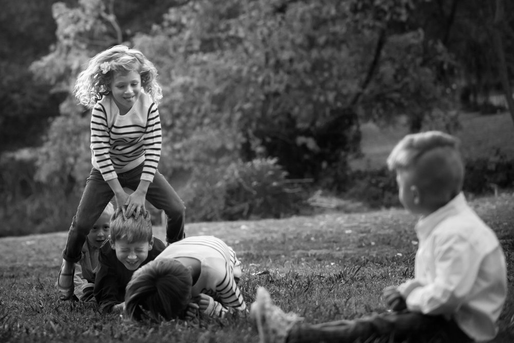 A girl leap-frogging over her brother on a lawn.
