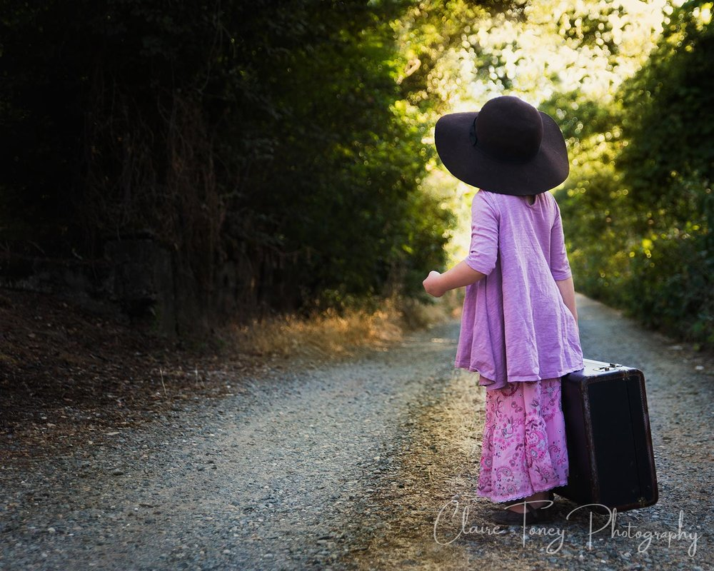 Little girl carrying a suitcase, wearing a hat, waiting. Claire Toney Photography, Sacramento Photographer