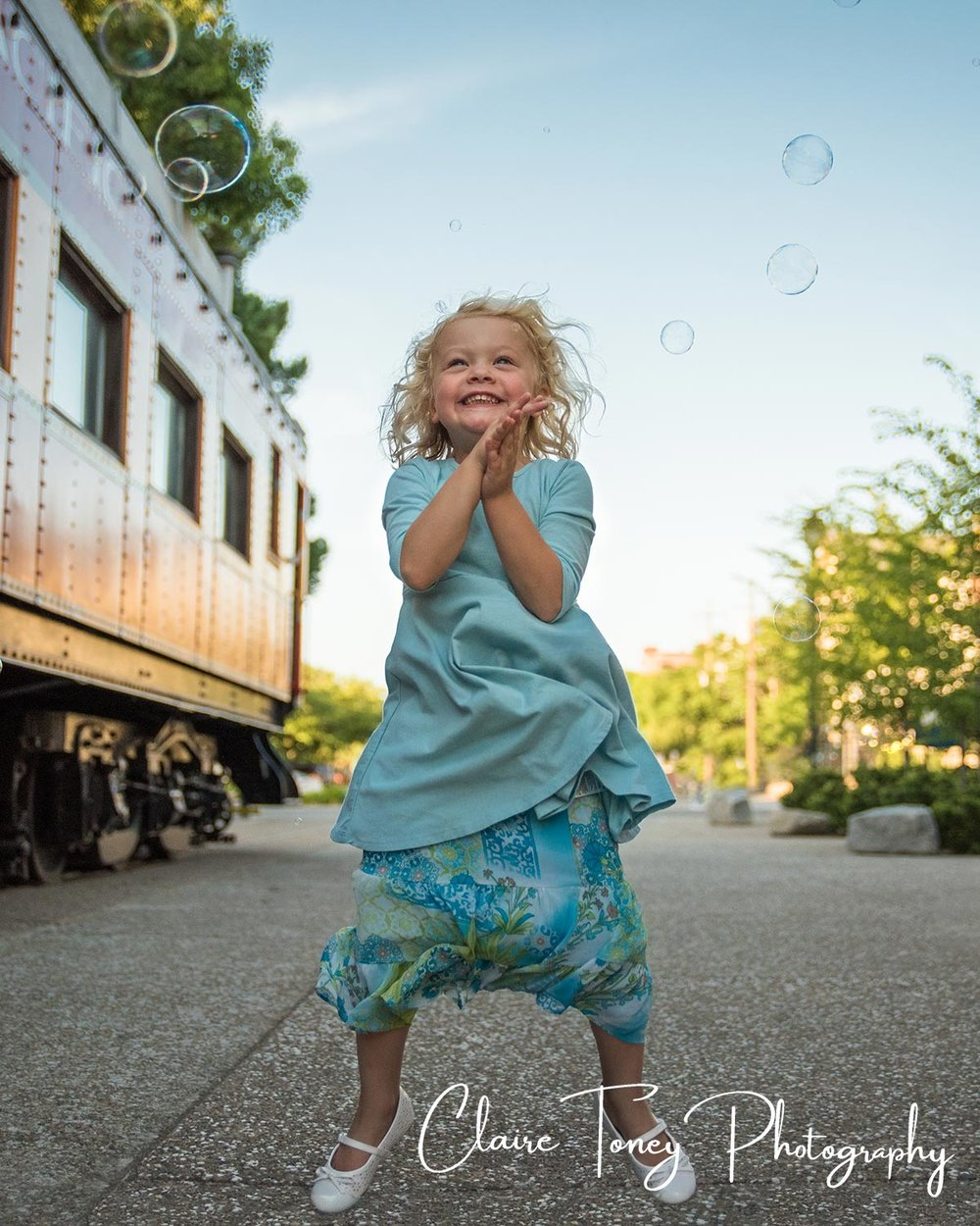 Little girl jumping for joy with bubbles surrounding her. Child photography. Claire Toney Photography, Sacramento Photographer