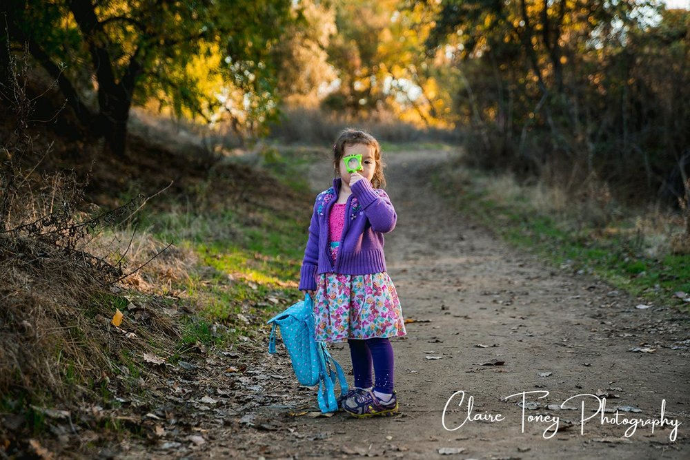 Little girl holding a magnifying glass to her eye and standing in the middle of nature trail