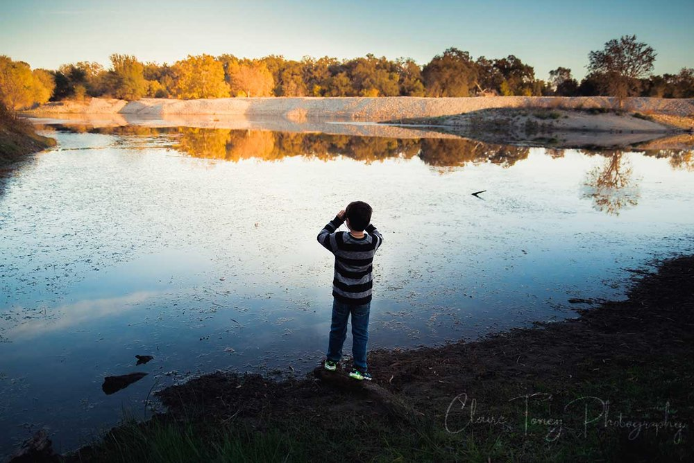 Boy looking out over a lake with binoculars