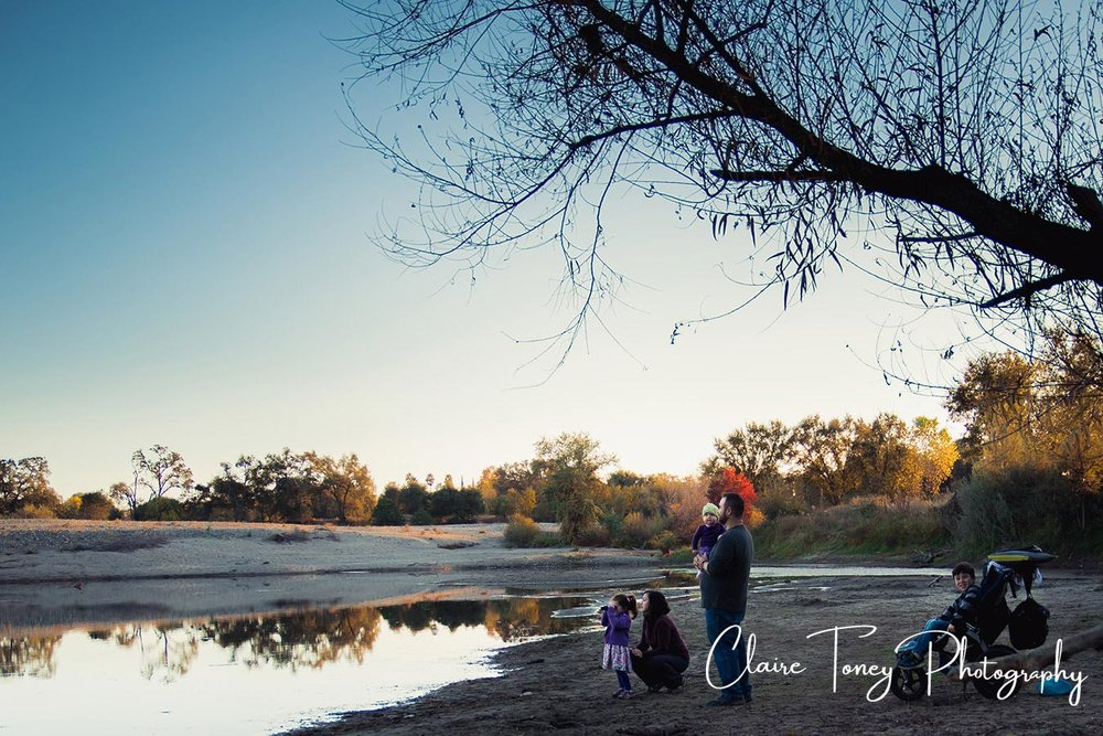 Girl looking through binoculars over a river with her family behind her and older brother in a stroller